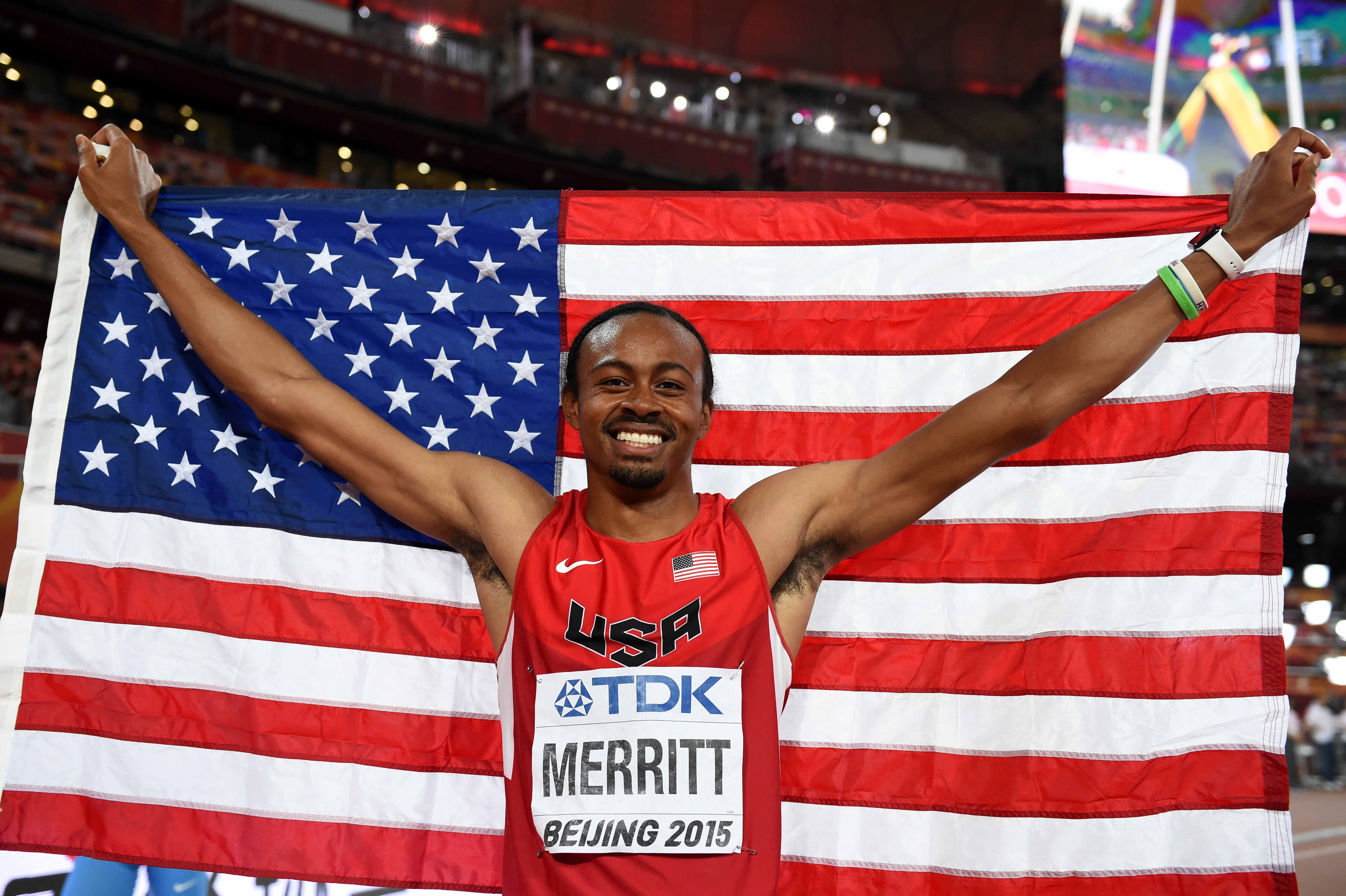 "Bronze medallist USA's Aries Merritt poses with his national flag after the final of the men's 110 metres hurdles athletics event at the 2015 IAAF World Championships at the ""Bird's Nest"" National Stadium in Beijing on August 28, 2015.  AFP PHOTO / FRANCK FIFE"
