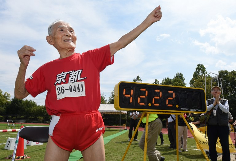 TOPSHOTS Hidekichi Miyazaki (in red), 105, imitates the pose of Usain Bolt after running with other competitors over eighty years of age during a 100-metre-dash in the Kyoto Masters Autumn Competiton in Kyoto, western Japan, on September 23, 2015. Miyazaki was authorised as the oldest sprinter who competed in a 100-metre-dash by the Guinness World Records.      AFP PHOTO / Toru YAMANAKA